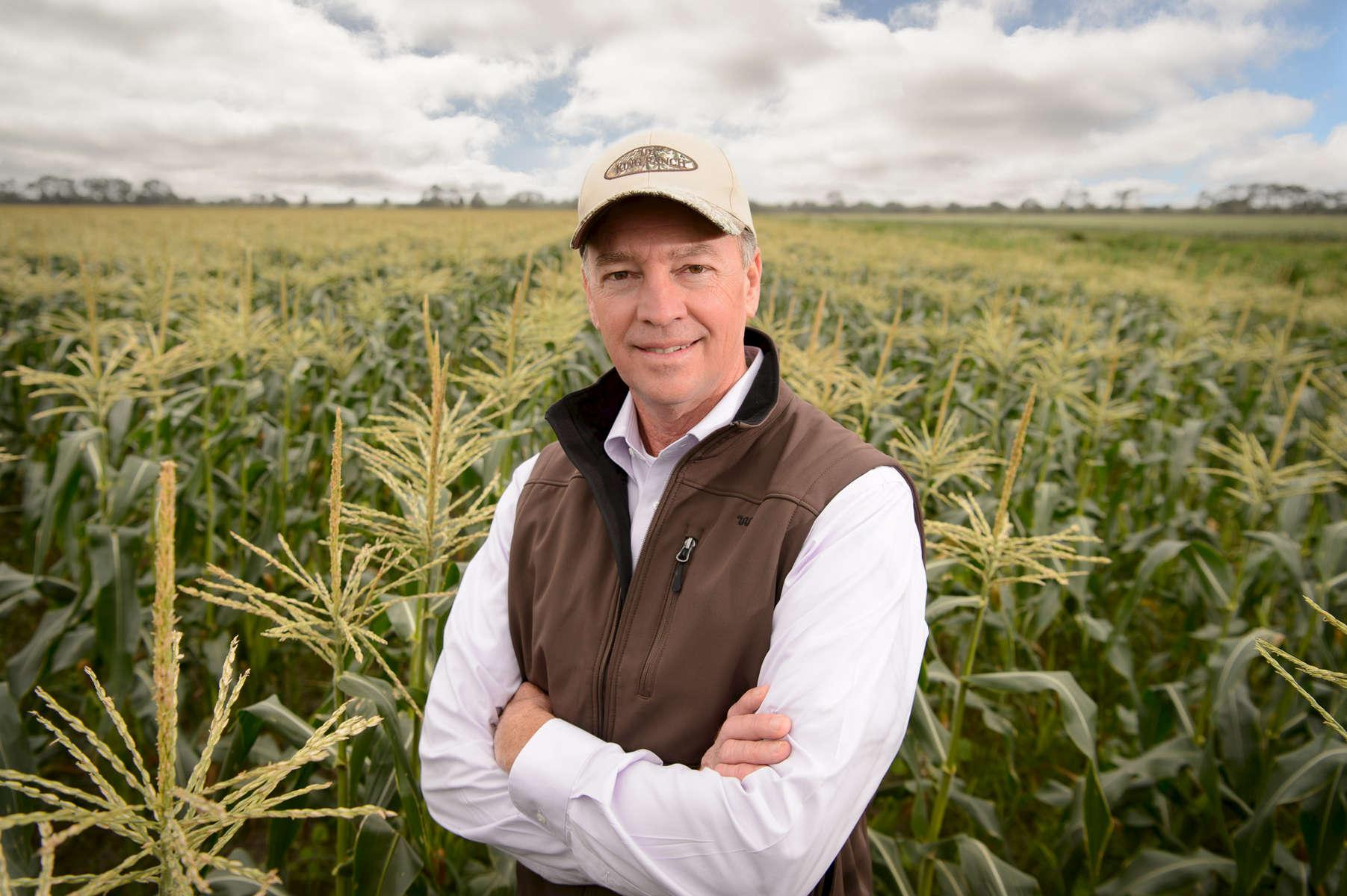 Farmer posing for a portrait in a corn field.