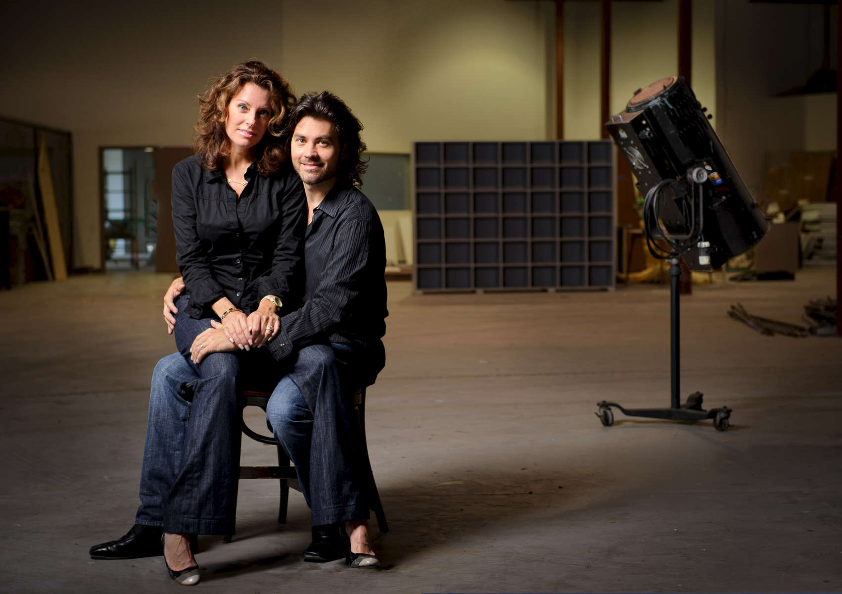 Couple posing for a portrait inside an empty studio
