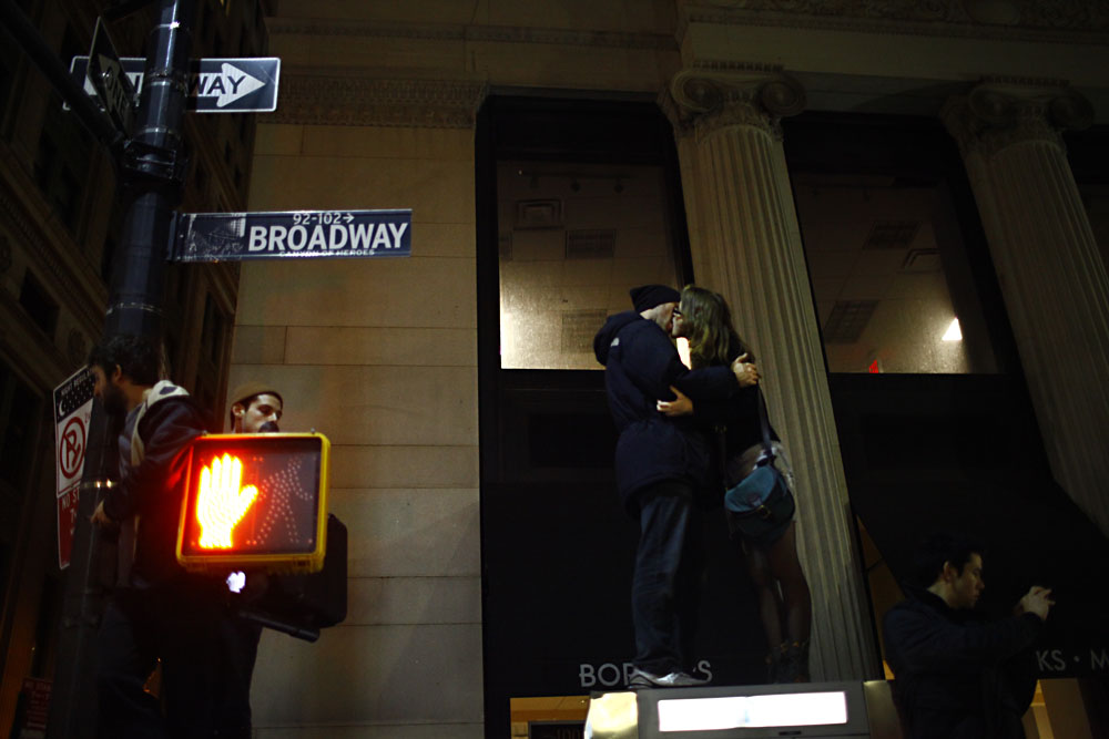 Two Occupy Wall Street protestors kiss atop a telephone booth.  New York Police evicted Occupy Wall Street protestors from Zuccotti Park on November 15, 2011.