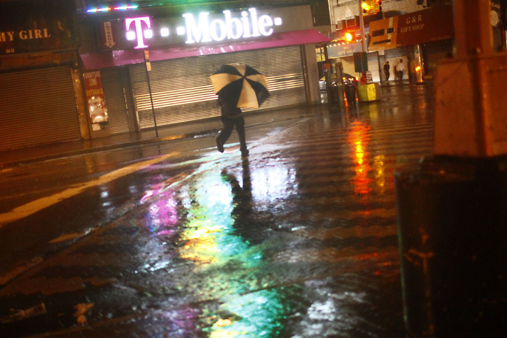 A man dashes across Jamaica Avenue as rains from Hurricane Irene intensified.