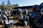 Soldiers gather their equipment after it was downloaded off the bus upon after arriving at Camp Blanding.