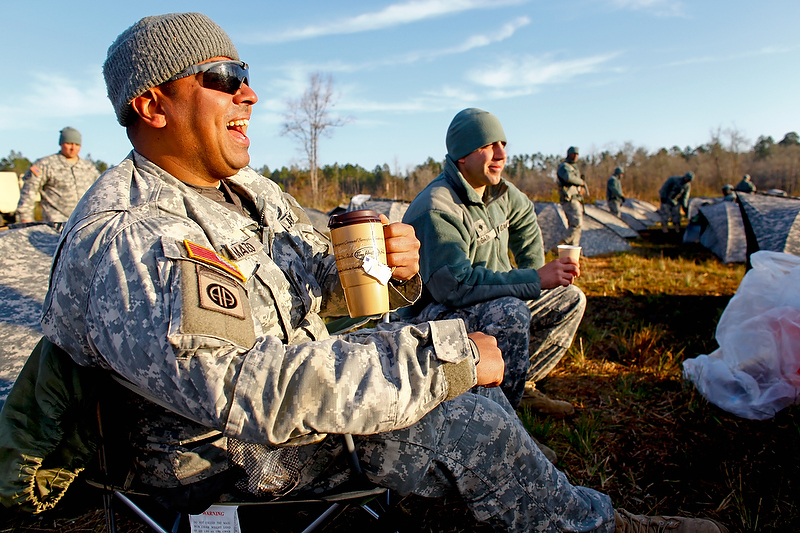 Sgt. Mateo enjoys some early morning coffee while sharing a joke with fellow soldiers.