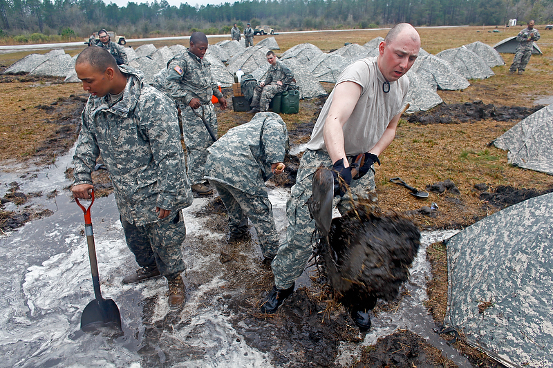 After heavy rainfall, soldiers dig trenches to drain the water from their living area.