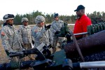 Soldiers speak to an artillery instructor on how to properly use their cannons.