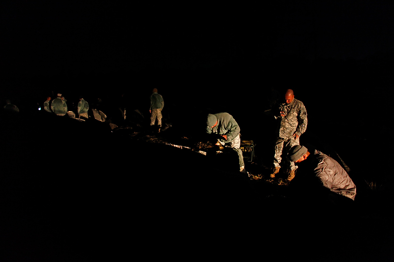With only the assistance of Humvee headlights, soldiers try to ready themselves for the training day.