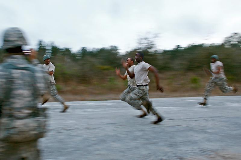 A group of soldiers race on the road for fun.