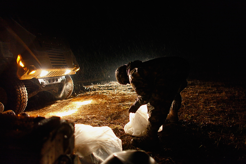 A soldier collects up unused gun powder during a heavy rain storm.