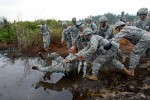 As part of his initiation into the battery, Pfc. Marte is thrown into a muddy pit.