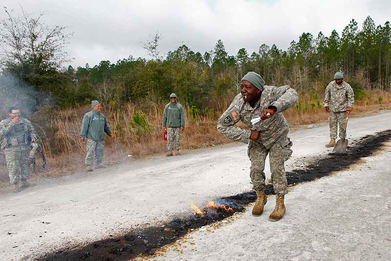 Staff Sgt. Brown does a celebratory dance as the unused gun powder is burned on the road. The powder burning signified the end of training.