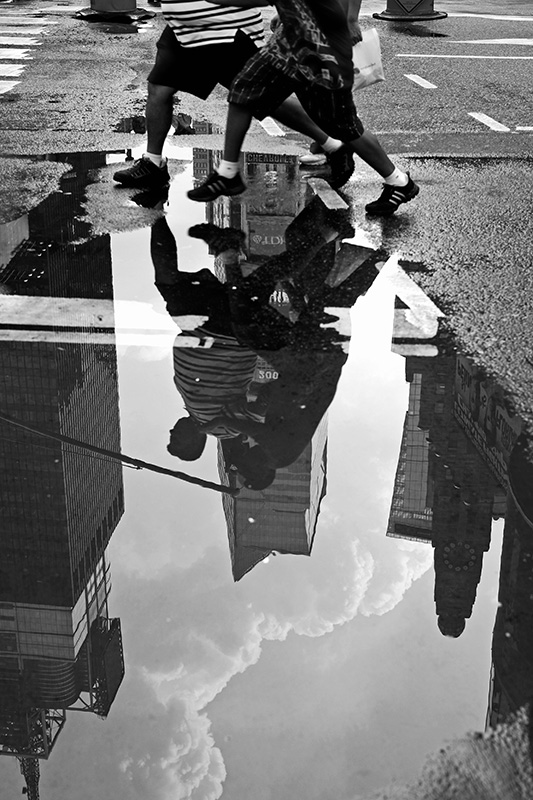 Two boys jump over a puddle in Times Square after a short rain shower on July 27, 2009.