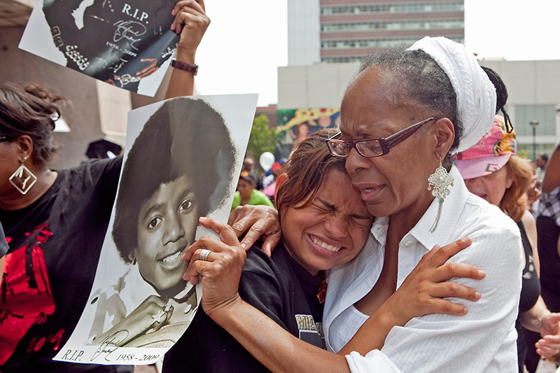 Jessica Salazar (left) is consoled by another fan when she is overcome with grief during the public broadcast of Michael Jackson's memorial service in Harlem on July 7, 2009.  Fans came out in droves to remember Jackson.