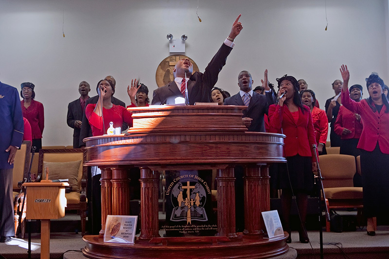 United Church of Jesus Christ Elder Richard McDonald (center) worships with his congregation on Dec. 27, 2009.