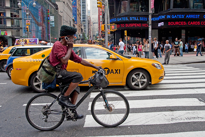 A man rides his bike while talking on his cell phone on 7th Avenue in Times Square, July 24, 2009.