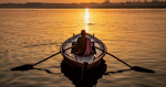 Man rowing a longtail boat on the Ganges River, Varinasi, India