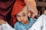 Young monk getting his head shaved in Burma