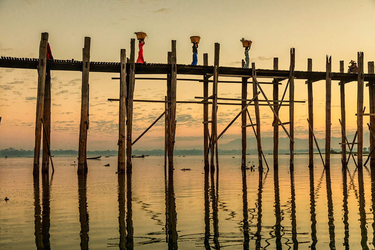 Women walking across the Ubein Bridge in Burma
