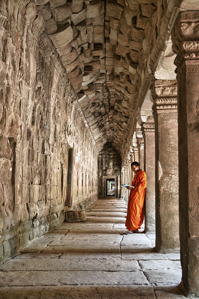 Monk reading inside Angkor Wat Temple