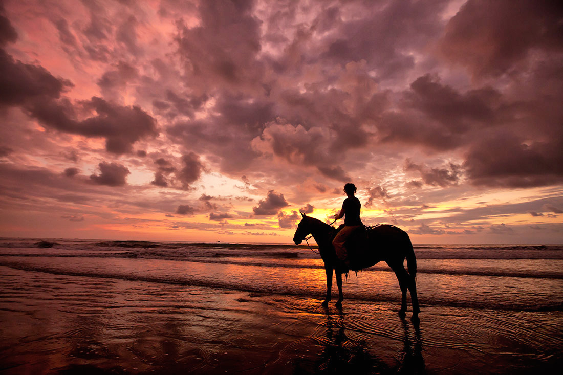 Riding horses in Costa Rica at sunset