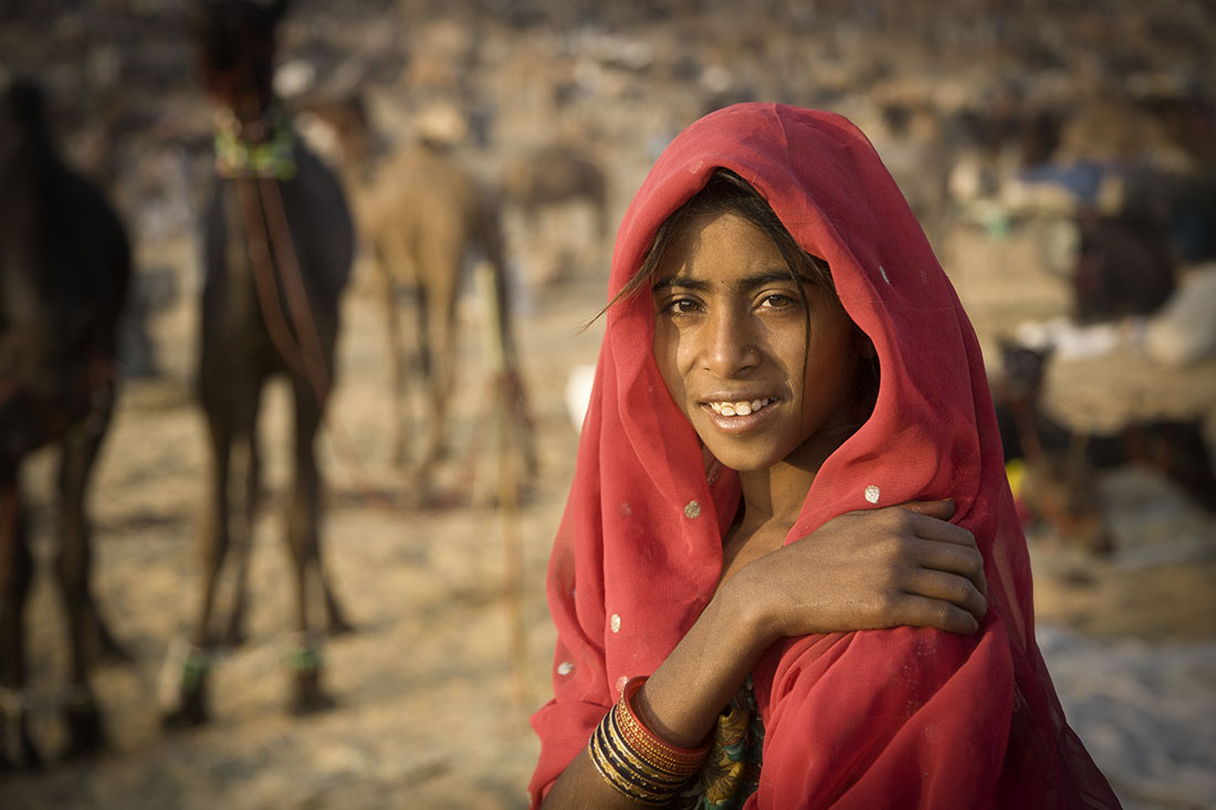 Beautiful young girl with red scarf at Pushkar