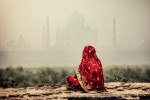 Woman across the river behind the Taj Mahal