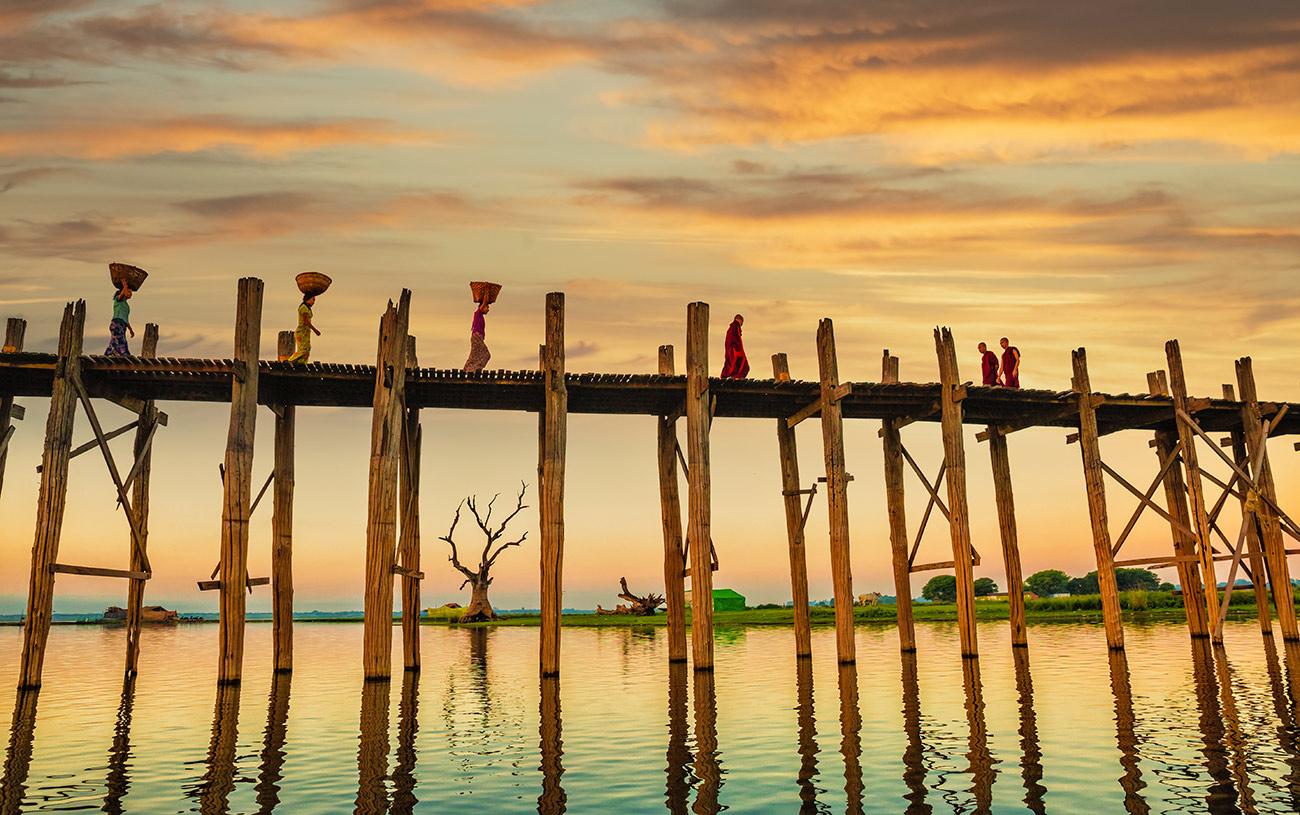 Monks and woman walking on The Ubein Bridge, Burma