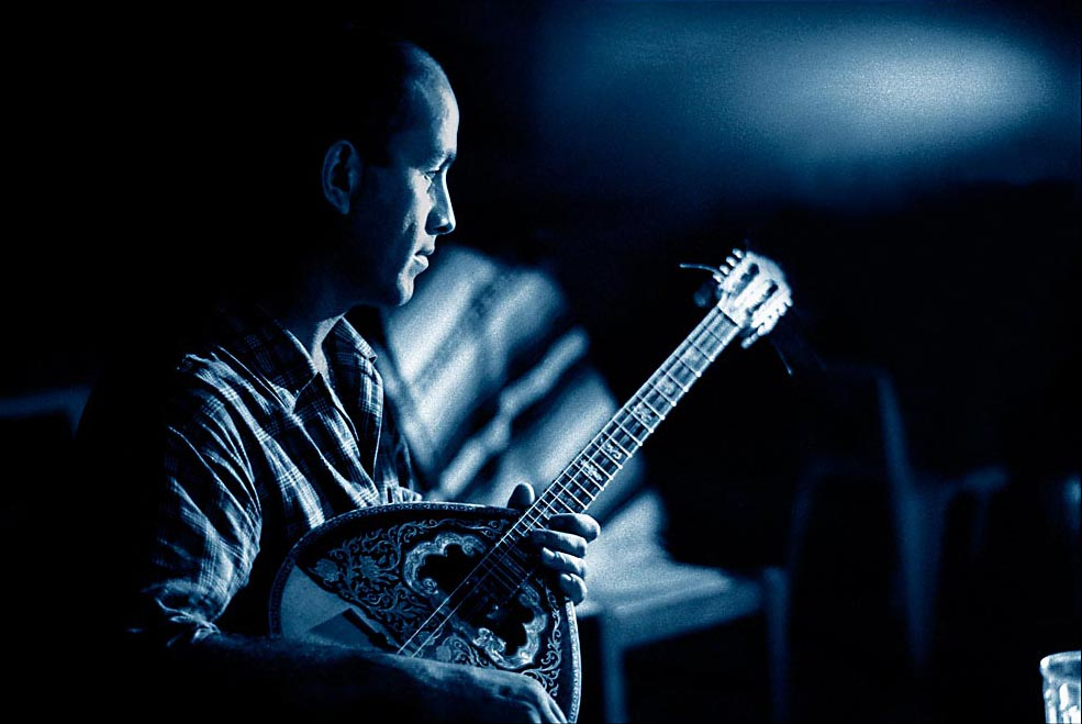 This is an intimate, moody, high contrast photograph of a man named George playing his bouzouki on the balcony.