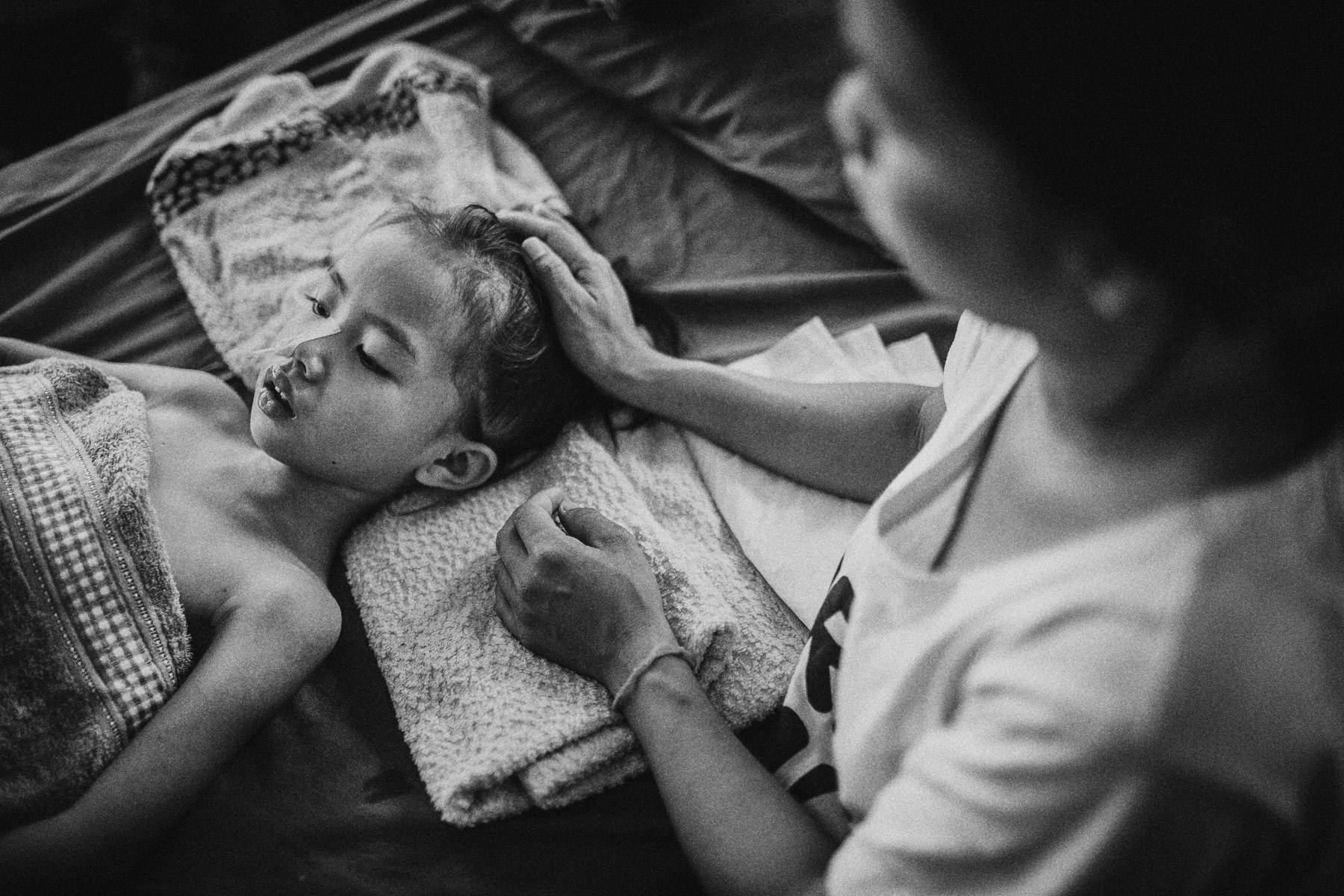 Six-year-old Namfon lies in a Japanese Encephalitis-induced coma at a hospital in Vientiane, Laos, as her mother Teo leans over to comfort her.