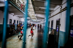 Inmates exercise and run laps in a small cell block corridor in Klong Prem Prison in Bangkok, Thailand.