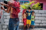Young children watch a procession of penitents atone for their sins during Holy Week in the Philippines.