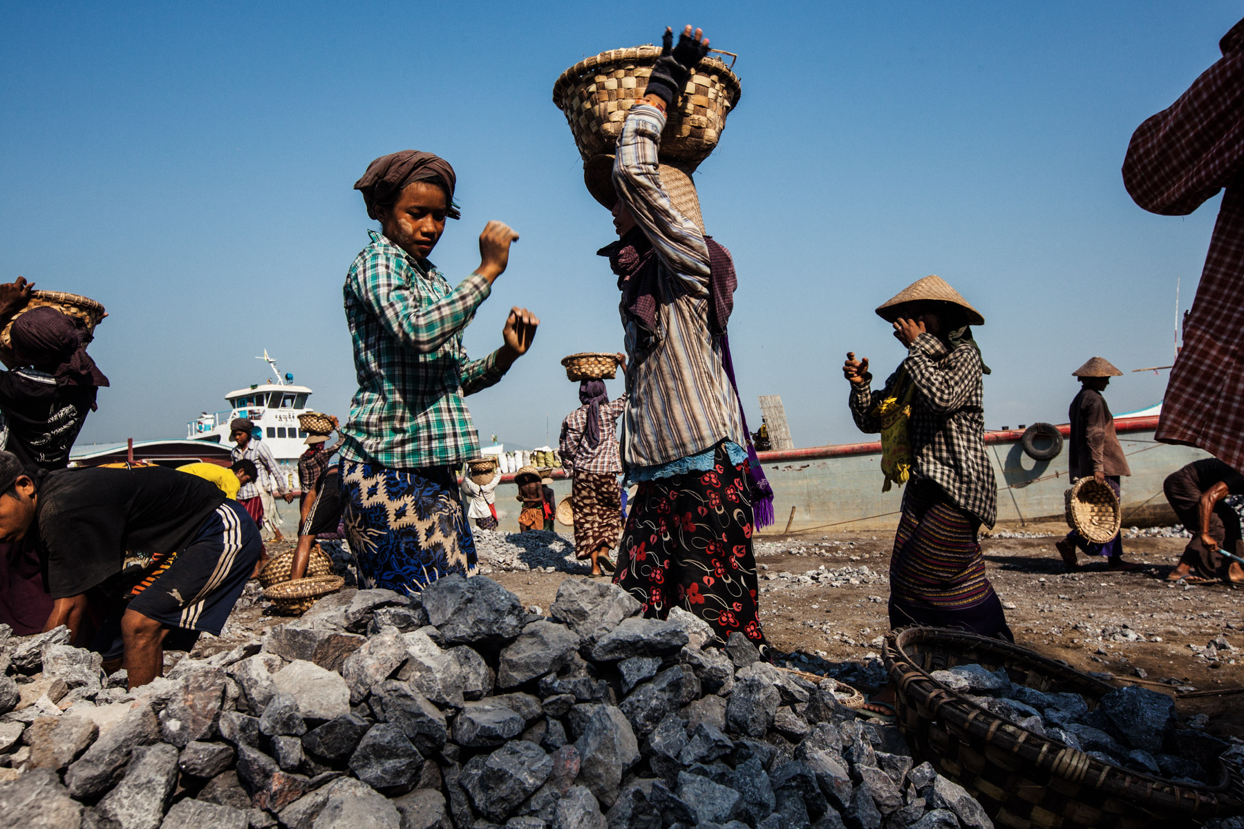 Burmese laborers load stones onto a large barge awaiting transport to construction sites downriver from Mandalay.