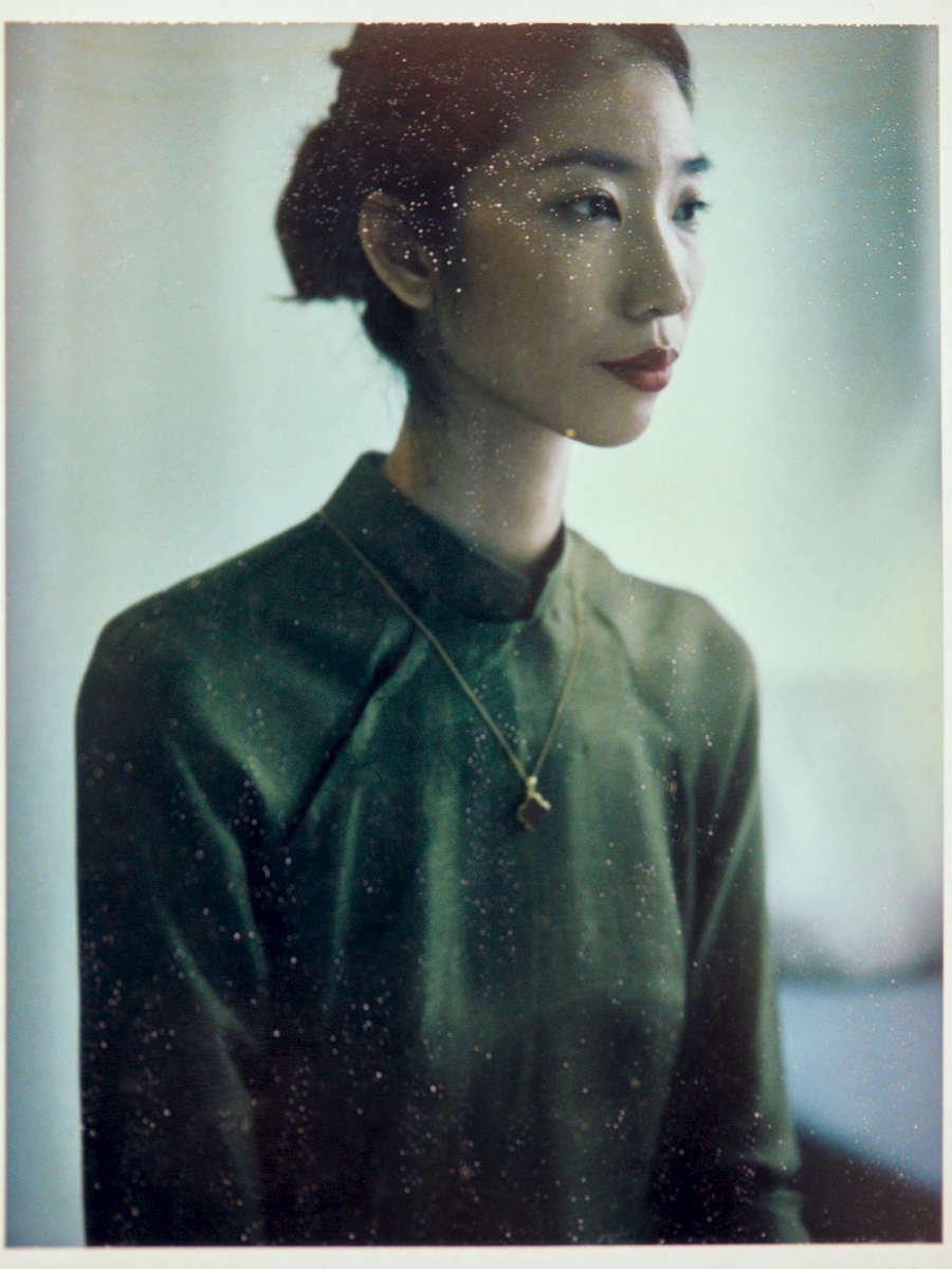 A Polaroid of a young Vietnamese woman in ao dai and a golden necklace, shot for Anāme in Saigon.
