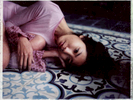 A Polaroid of a young woman in a pink top on a blue-tiled floor at an old home in Hanoi, Vietnam.