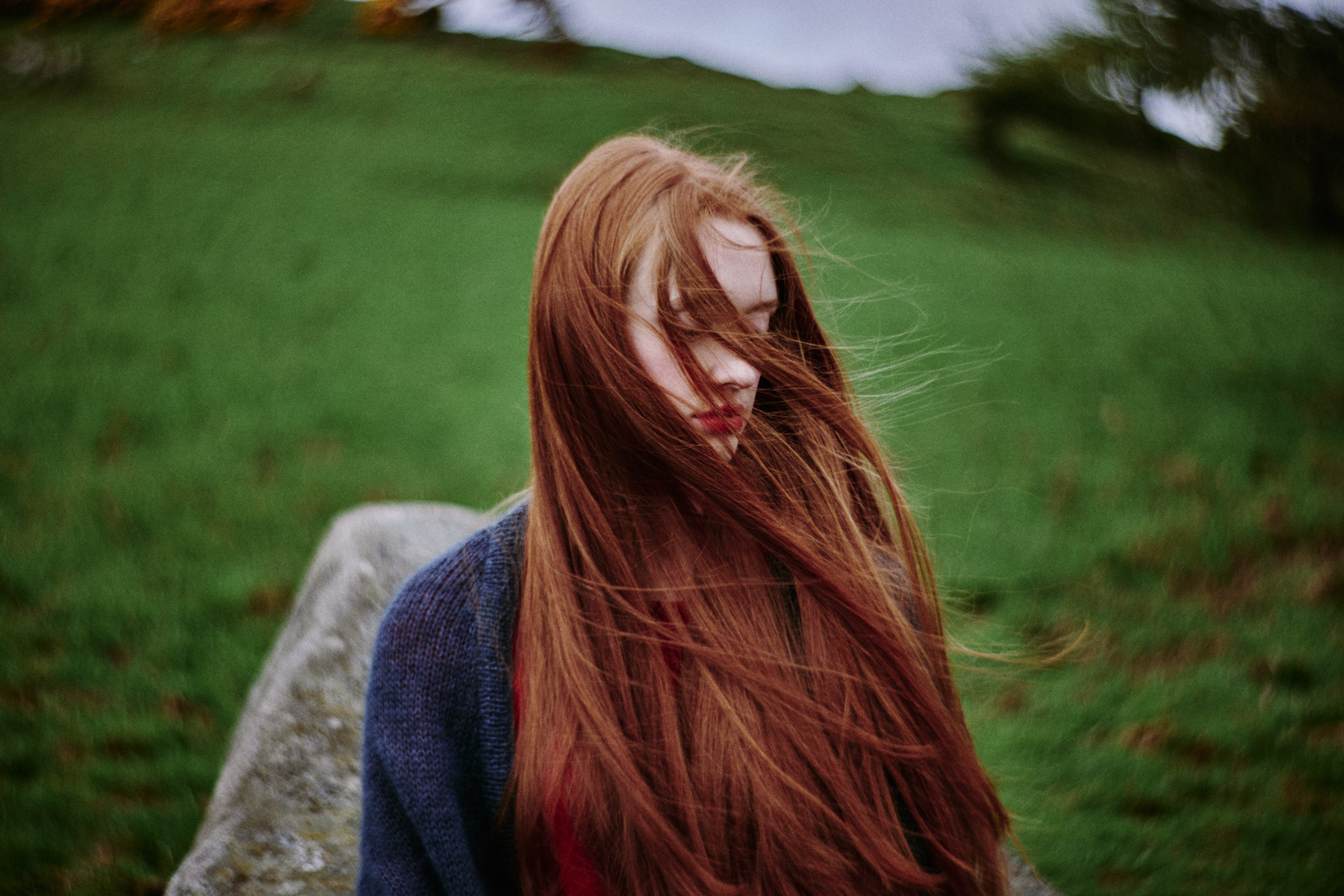 The wind swirls a woman's hair in the countryside of northern Scotland.