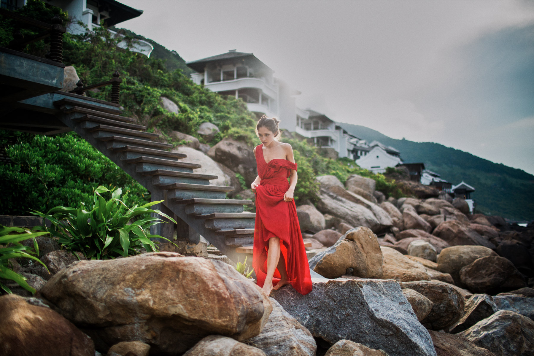 A young woman walks across rocks at the Intercontinental Sun Peninsula Resort in Danang, Vietnam.