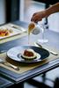 A waiter pours anglaise sauce over a dessert at the Hotel de la Coupole in Sapa, Vietnam.