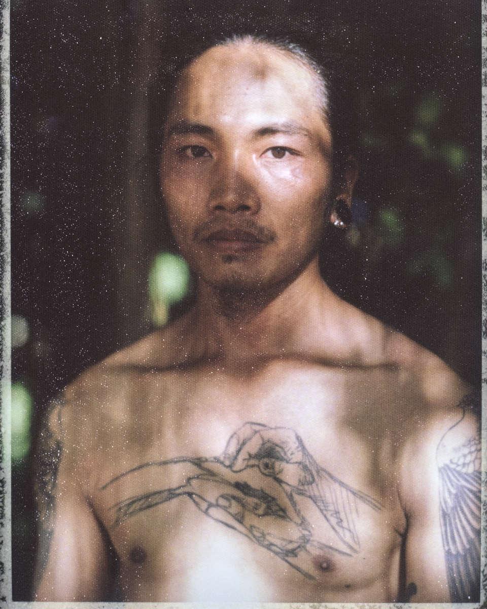 A young Vietnamese man in dappled sunlight.