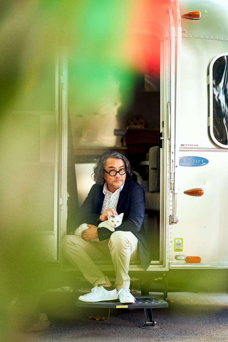 A portrait of architect Duangrit Bunnag with his cat and Airstream trailer in Bangkok, Thailand.