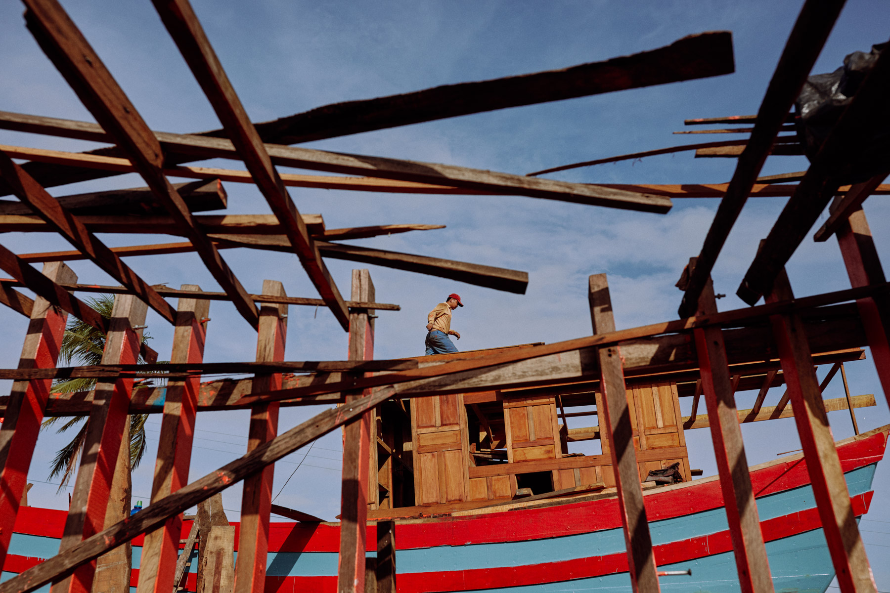 A man walks a plank at a boat construction yard in central Vietnam.