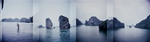 A panorama view of karsts and boats and a man walking in Halong Bay in northern Vietnam.