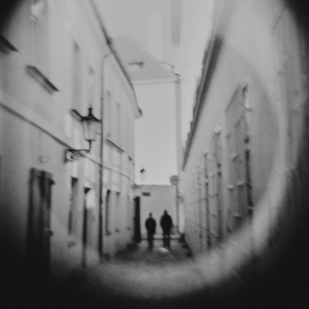 Two men walking in a narrow alley in Prague.