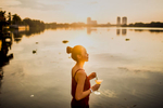 A young woman stirs a cocktail on the banks of the Saigon River.