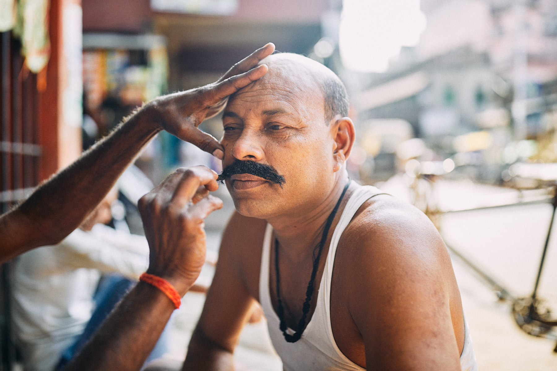 A man gets his mustache dyed on the streets of Kolkata, India.