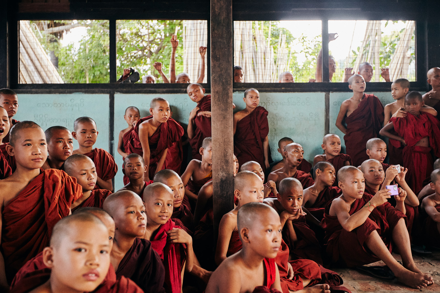 A group of novice Burmese monks watch a performance in a small town outside of Mandalay, Myanmar.