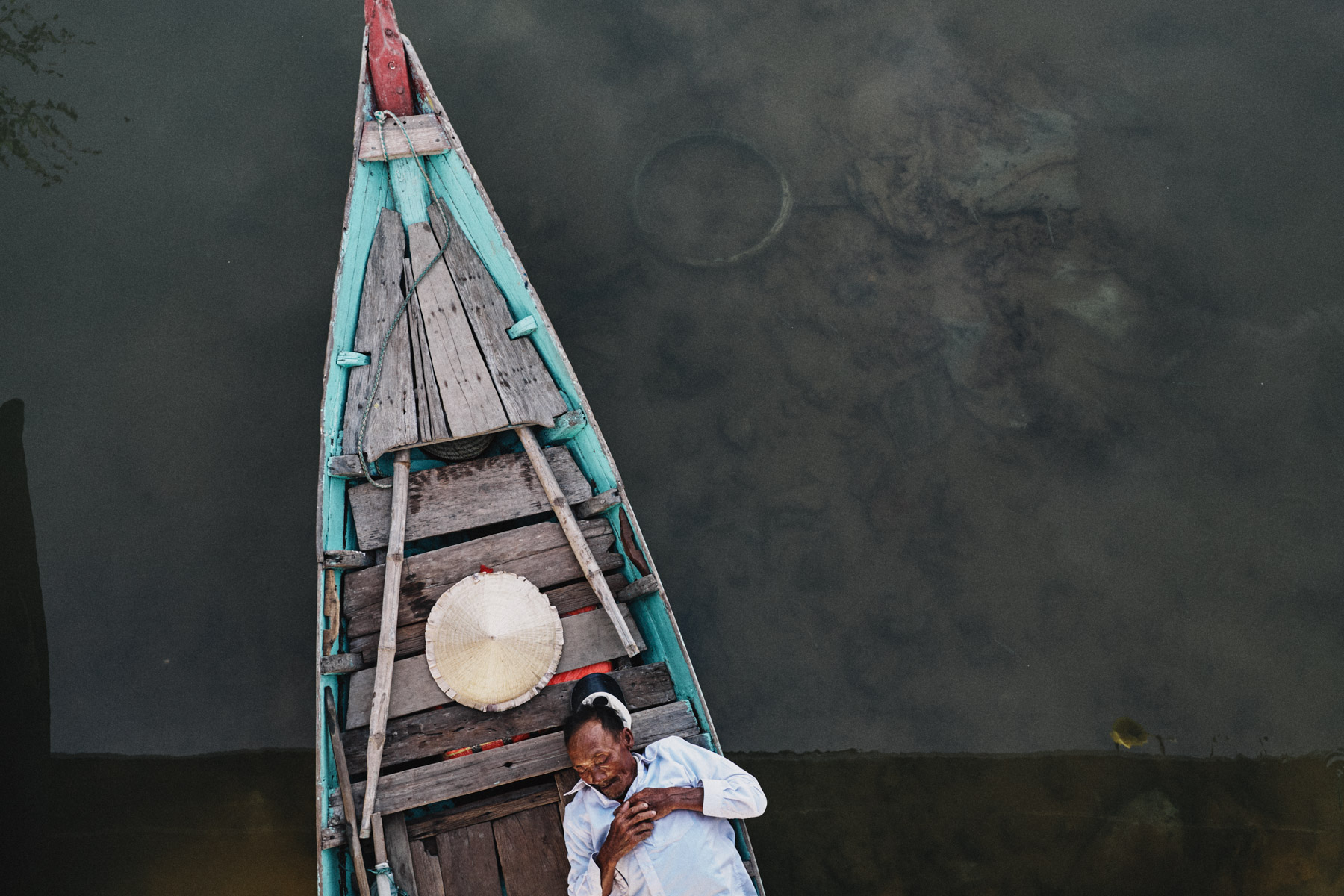 A fisherman takes an afternoon nap beneath a bridge on the Thu Bon river in Hoi An, Vietnam.