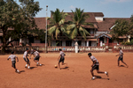 Schoolboys play a game of football in a dirt lot in Margao, India.
