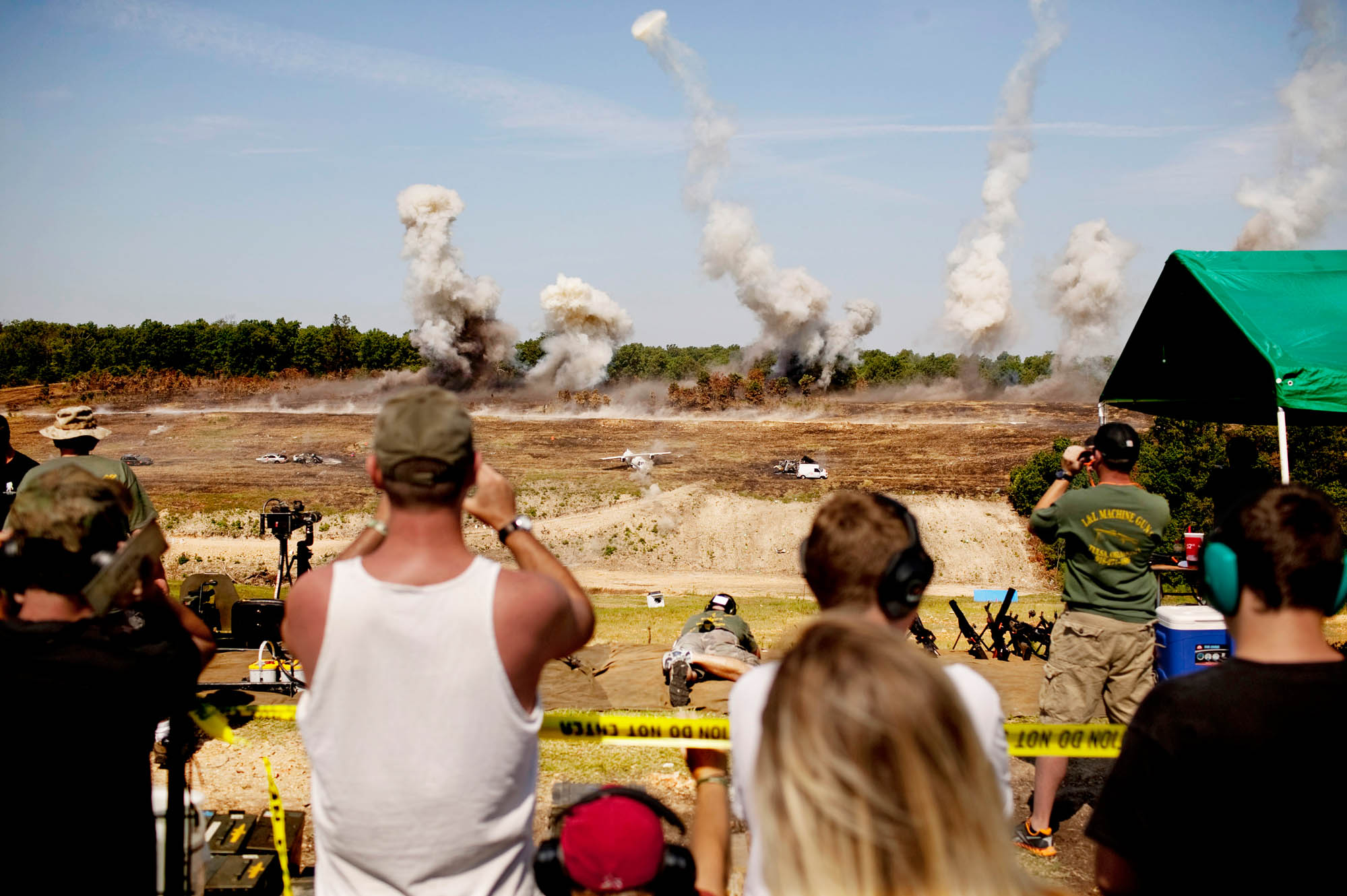Spectators look on as a series of planned explosions kick off the day's first round of live fire. An explosive ordinance team placed dozens of  charges throughout the range to enhance excitement for shooters and spectators.