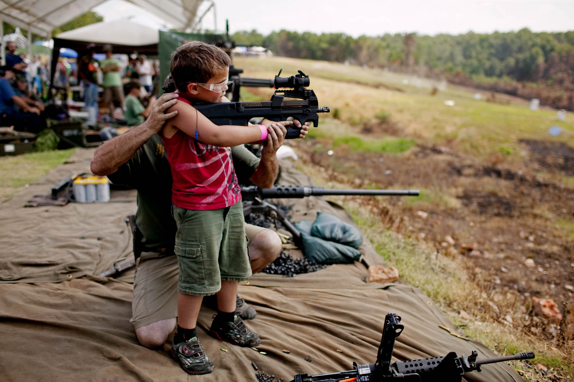 A young boy is supported as he fires a fully automatic machine gun. Safety regulations at OFASTS are extremely tight with all shooters carefully monitored by exhibitors.