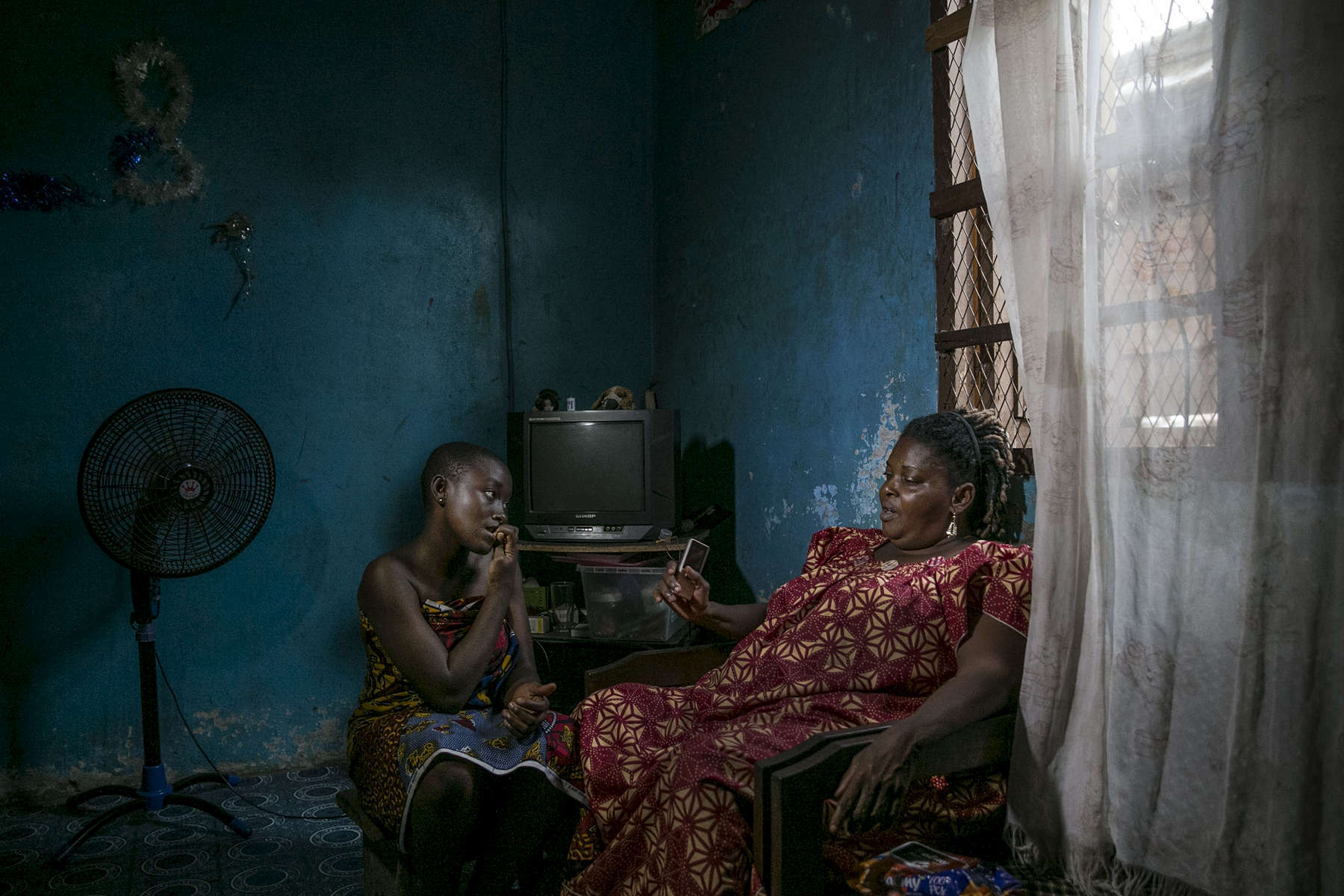 Sylvia Virginie Voua ( known as Aicha ) sits with her granddaughter, Roseline Nad, inside the main room of her compound. The buildings house numerous widows who lost their husbands during Ivory Coast's political crises.