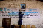 A bailiff hangs a photo of Congo's President, Joseph Kebila, on the main courtroom wall.