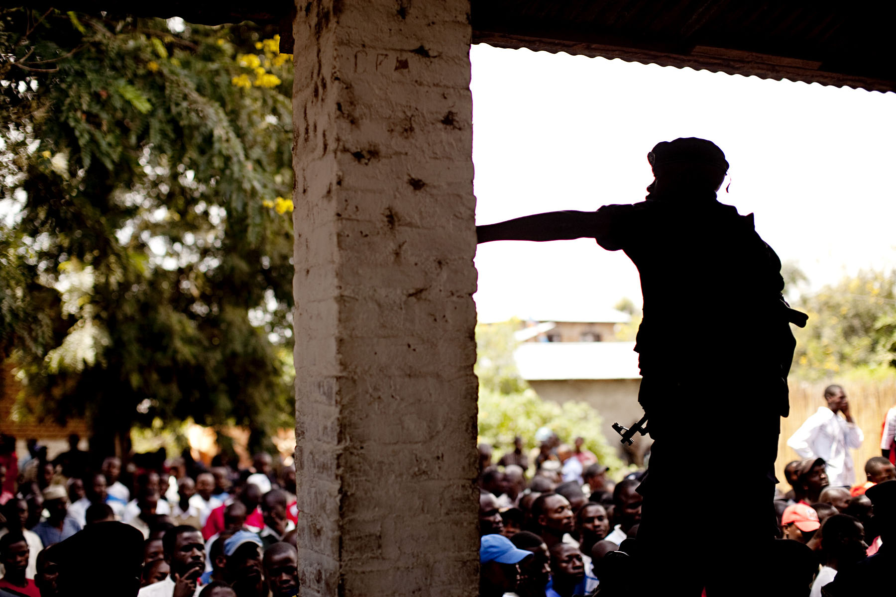 A Congolese police officer stands guard over huge crowds that turned out to watch the proceedings. Despite the blazing sun, hundreds forewent their typical duties in order to observe the trail.
